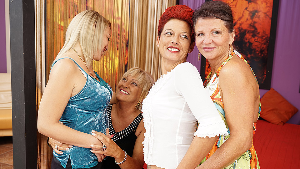 Four old and young lesbians having a party on bed
